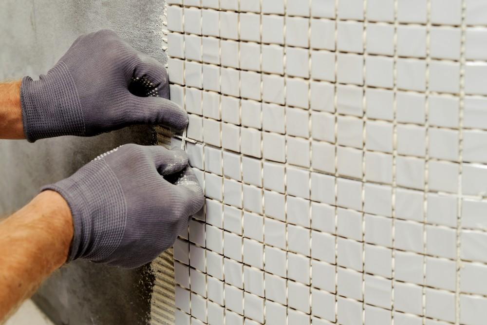 Процесс укладки мозаичной плитки в бассейне